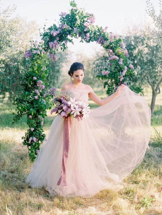 a lilac wedding arch and bridal bouquet are the ultimate spring romance