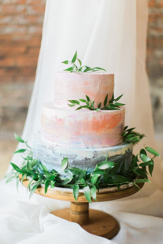 a watercolor coral and blue wedding cake with ombre effects and fresh greenery