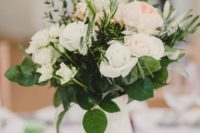 14 a white jug with lush neutral florals and greenery surrounded with candles for a natural chic look