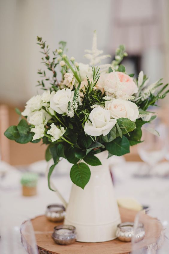 a white jug with lush neutral florals and greenery surrounded with candles for a natural chic look