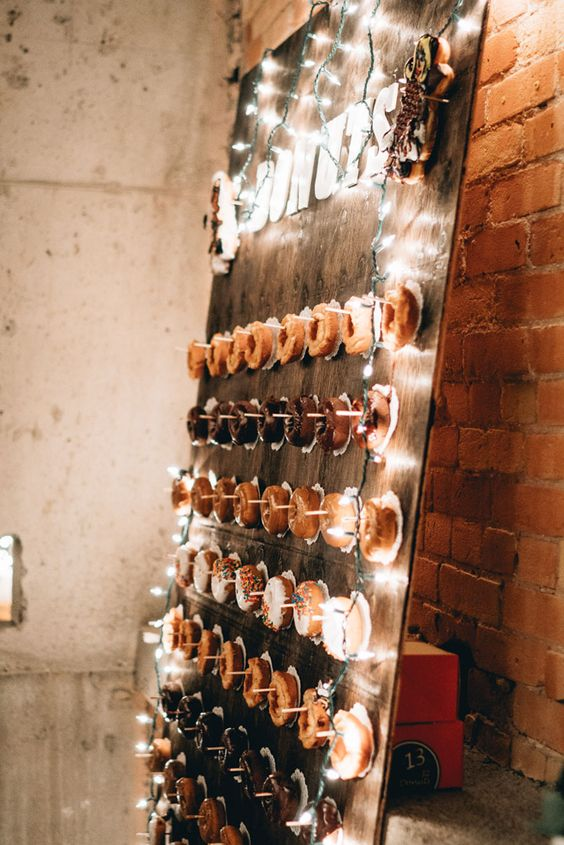 a wooden board donut wall decorated with LED lights for an industrial feel