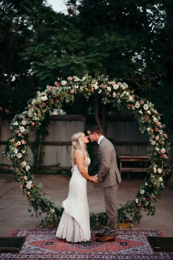 an oversized circle floral and greenery arch for a boho chic wedding