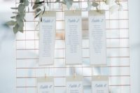 14 gold wire mesh reception table seating chart with pink and peach flowers and greenery