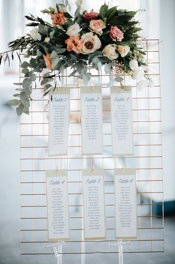 gold wire mesh reception table seating chart with pink and peach flowers and greenery