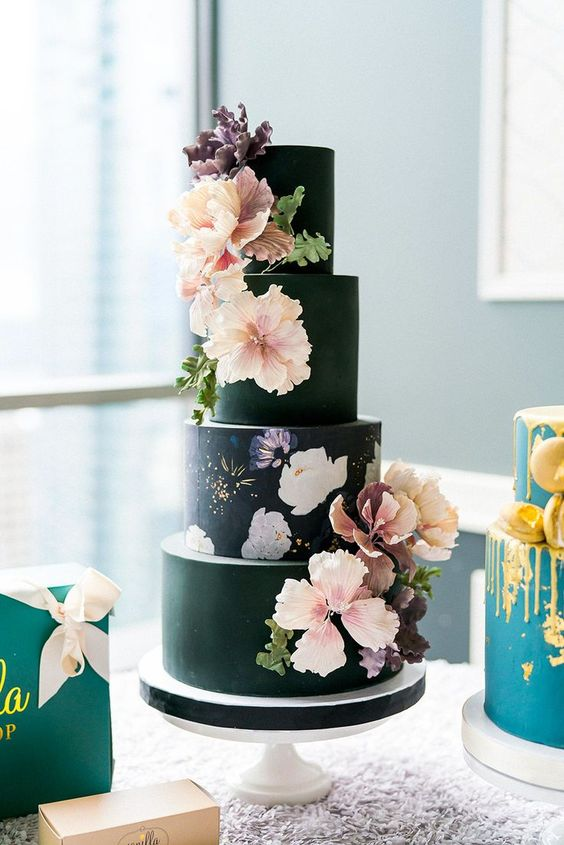a black wedding cake with floral painting and blush and purple blooms on it