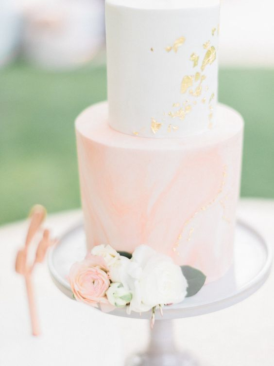 a marbleized peach pink and white wedding cake with gold leaf decor for a glam touch