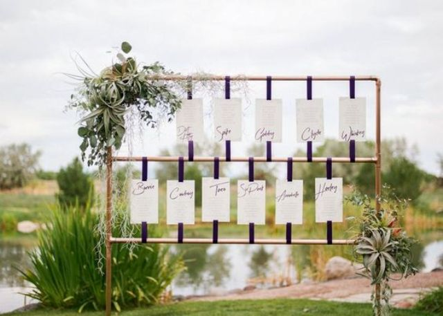 a modern copper stand seating chart topped with air plants and fresh greenery