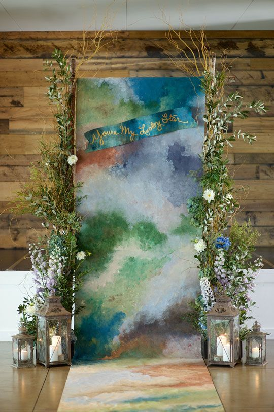 a very bold watercolor wedding backdrop with greenery and blooms on both sides plus lanterns