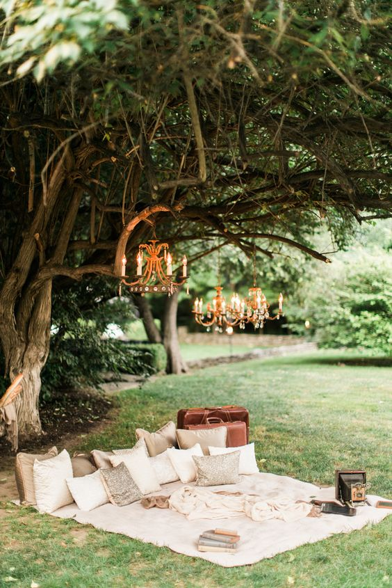 a vitnage picnic setting with a lot of pillows, glam chandeliers and some vintage items instead of a sweetheart table