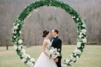 15 an oversized circle floral wedding arbor with lush greenery and white blooms is a very trendy solution