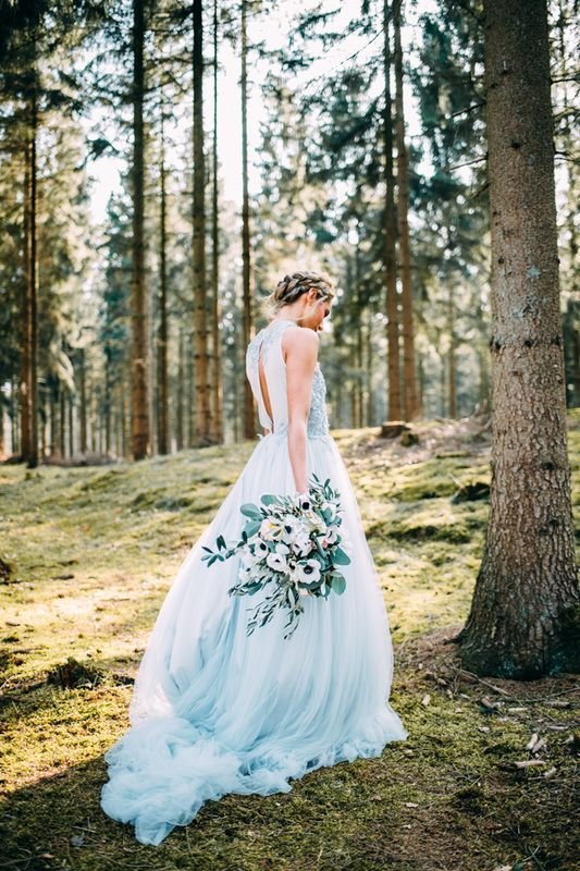 the bride wearing a light blue wedding dress with a back cut and an embellished bodice