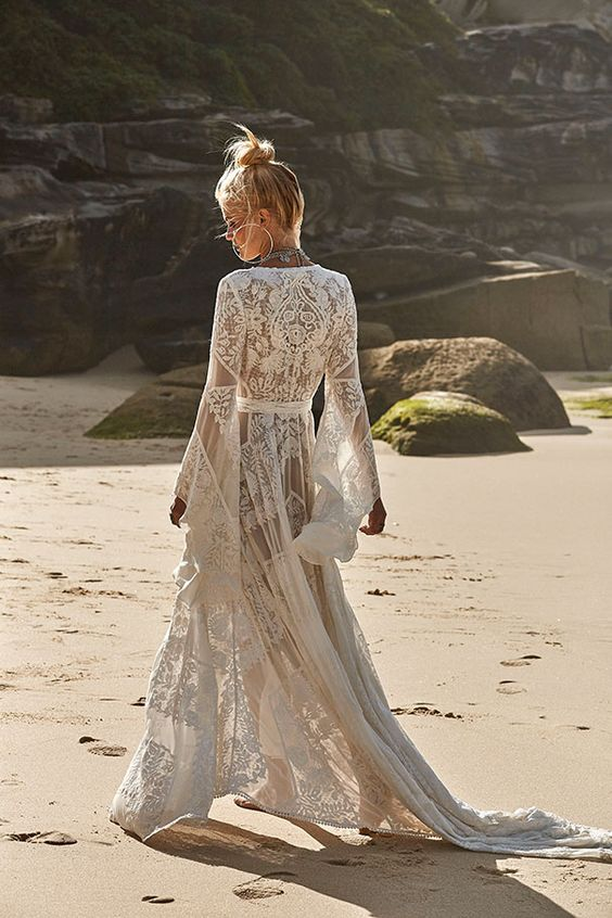 a gypsy-inspired boho lace wedding dress with a V-neckline, bell sleeves and a train