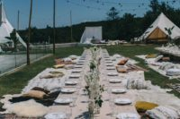 16 a simple picnic setting with neutral florals, lots of carpets and pillows and teepee all around
