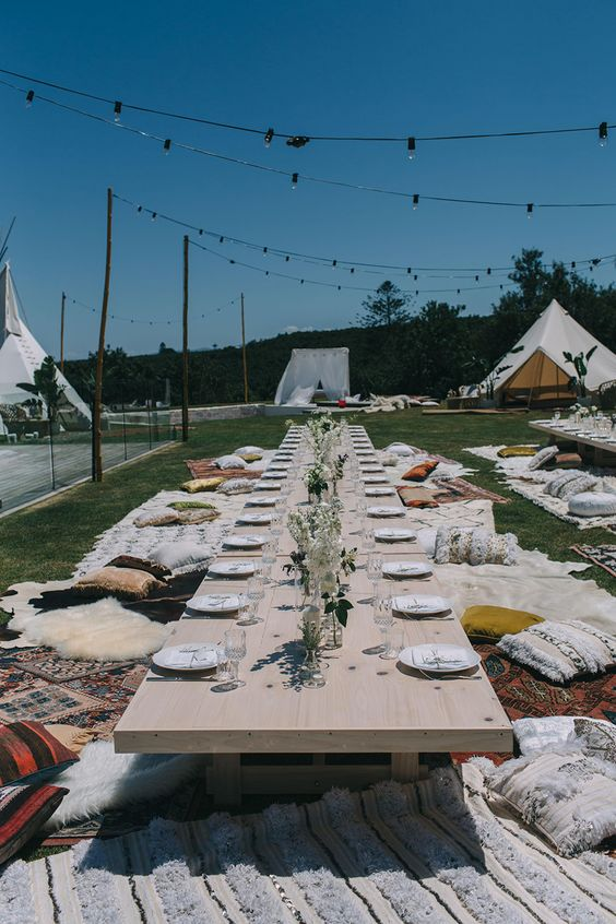 a simple picnic setting with neutral florals, lots of carpets and pillows and teepee all around