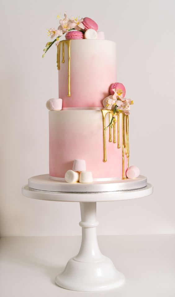 an ombre pink wedding cake with marshmallows, gold drip and macarons for a cute glam wedding