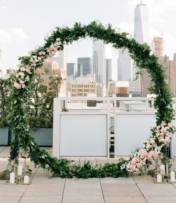 oversized greenery and blush bloom wedding arch with candles around will fit many wedding styles