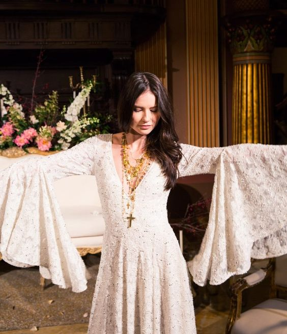 a gypsy inspired wedding dress with a deep V neckline, bell sleeves and embellishments