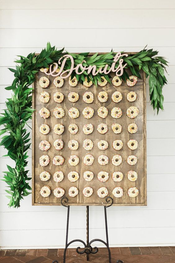 a lush greenery garland with calligraphy letters on the donut wall