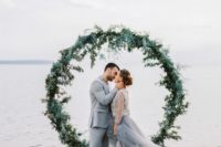 17 a lush greenery wedding arch right in the water for a seaside wedding