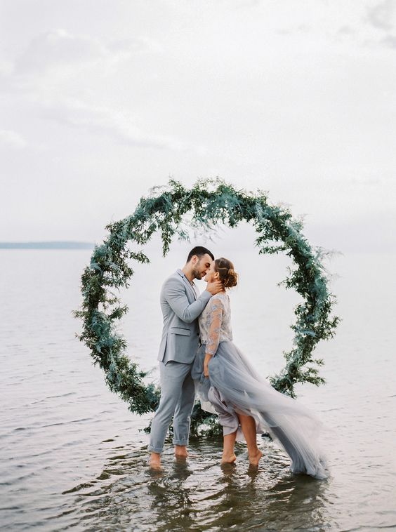 a lush greenery wedding arch right in the water for a seaside wedding