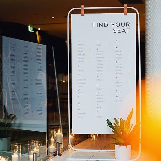 a simple white metal stand with a seating chart hanging on leather pieces is a creative idea
