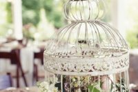 17 a vintage birdcage with greenery and neutral blooms for a chic centerpiece