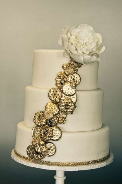 a wedding cake topped with edible gold coins and a sugar flower