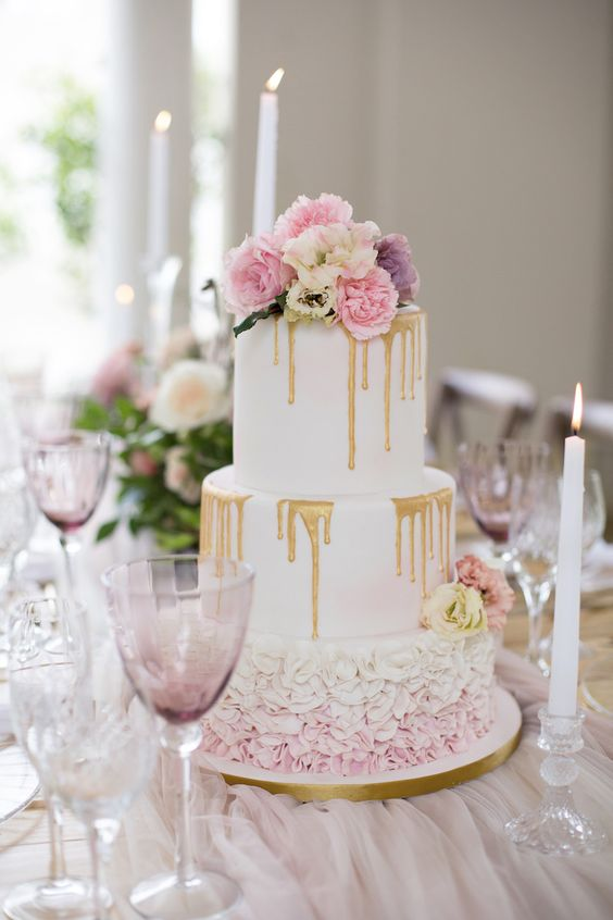 a wedding cake with pink and purple blooms, ruffles and gold drip