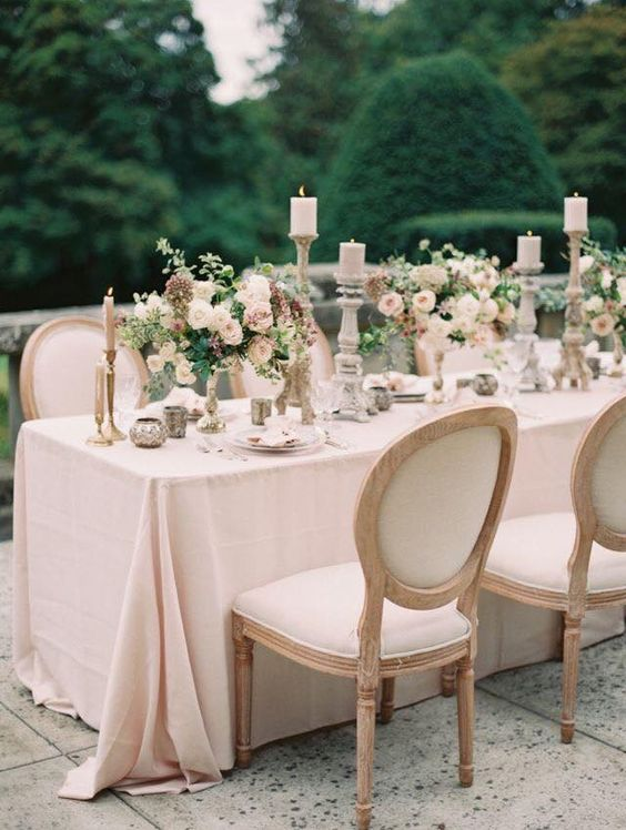 an al fresco table setting with blush details, florals and candles