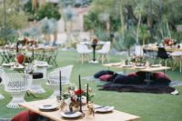 17 boho styled picnic wedding reception with low tables, moody textiles and black candles