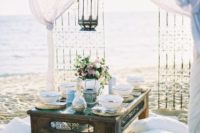 18 a Moroccan-style picnic setting on the beach, airy fabrics, a large lantern, Moroccan-inspired dishes and plates and pillows for sitting