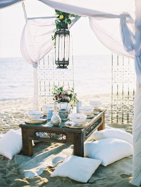 a Moroccan-style picnic setting on the beach, airy fabrics, a large lantern, Moroccan-inspired dishes and plates and pillows for sitting