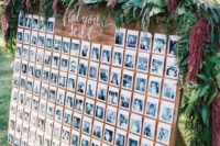18 a black and white photo seating chart topped with fresh greenery and flowers