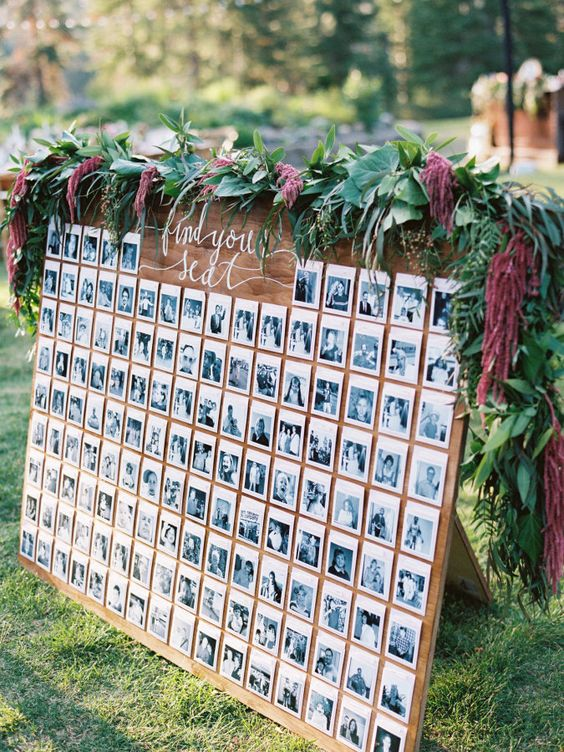 a black and white photo seating chart topped with fresh greenery and flowers