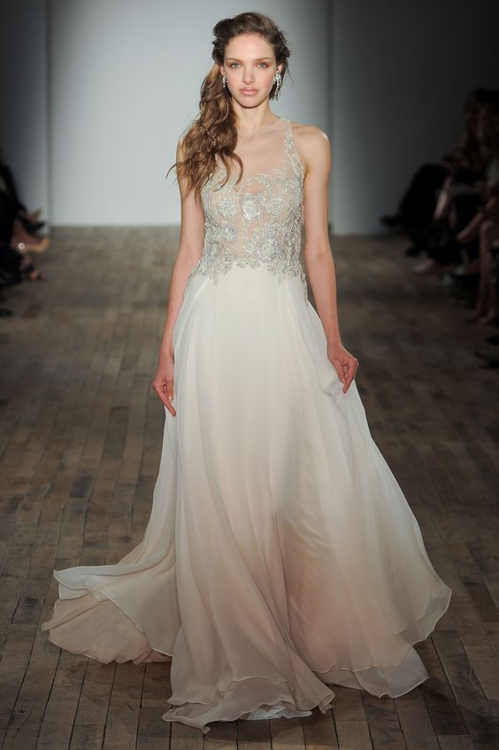 a creamy wedding gown on straps with a lace applique embellished bodice and a flowy skirt by Lazaro