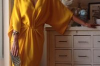 18 a sunny yellow kimono styled dress with wide sleeves, a small clutch with leather detailing