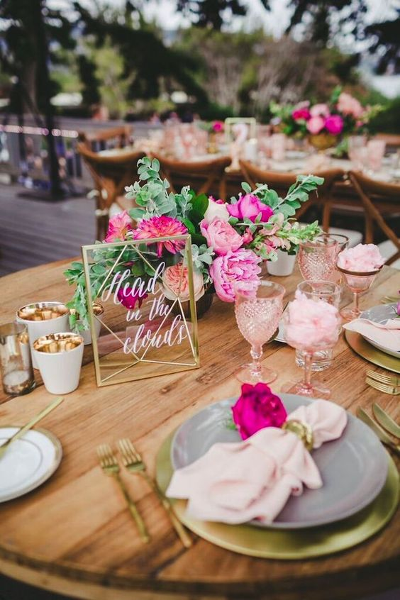 a table setting with gold touches and blush and hot pink blooms