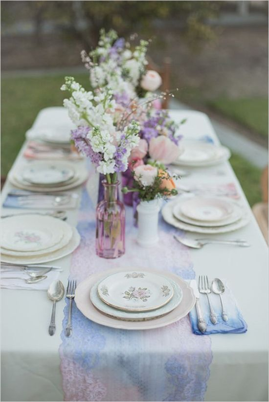 a watercolor wedding table runner in pink and blue with a lace trim and matching blooms