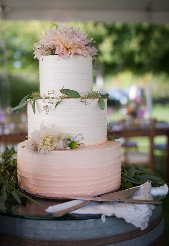 an ombre buttercream blush wedding cake with blush blooms and eucalyptus on top