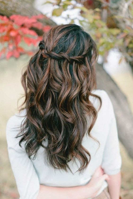 a chic twisted halo wavy half updo looks especially interesting with balayage