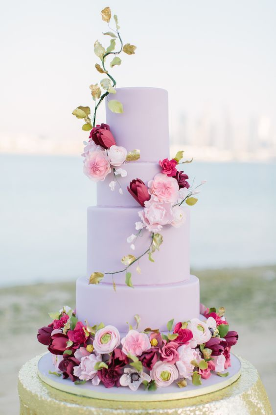 a lavender-colored wedding cake with lots of sugar blooms for a more formal wedding