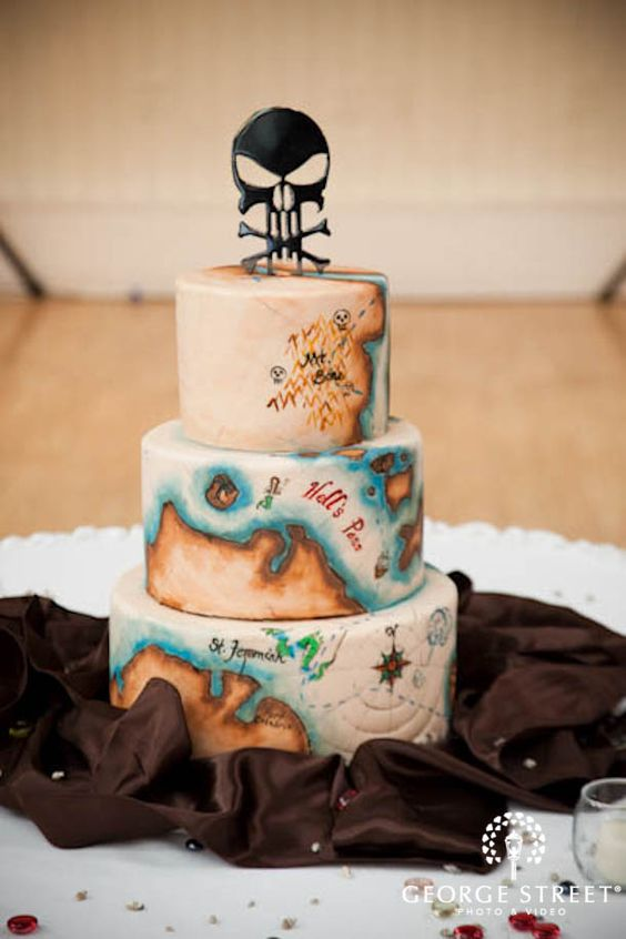 a pirate wedding cake with a vintage sea map and a skull topper