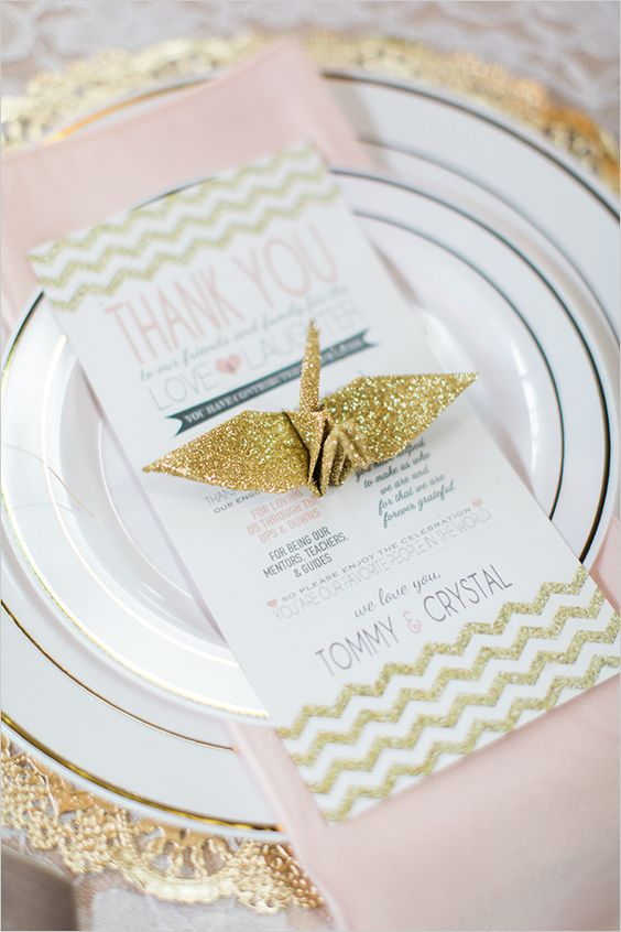 a place setting in blush and gold glitter with a glitter paper crane and a lace edge charger