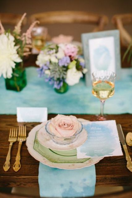 a watercolor place setting with a blue to green ombre watercolor menu and a matching napkin