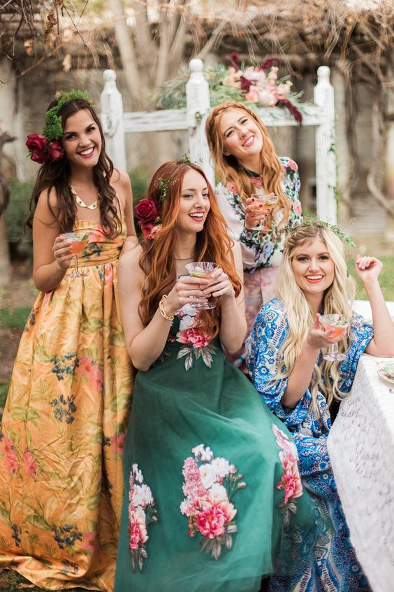 girls in mismatched floral gowns of different shades and prints ready for a boho wedding