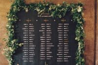 20 a chalkboard seating chart done with a chalk pen and decorated with a fresh greeneyr garland