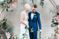 20 a large tropical-inspired wedding arch covered with bold leaves and blooms and candles around