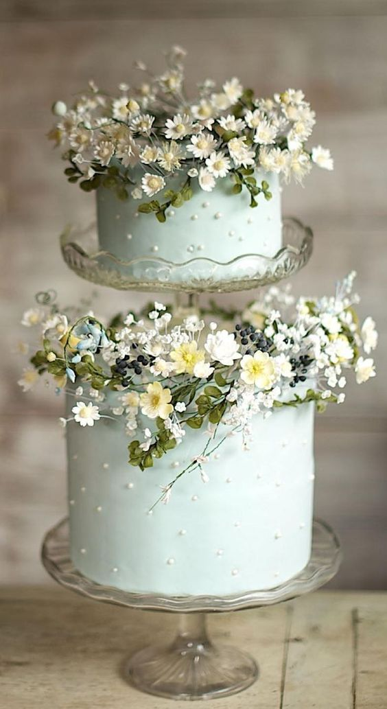 a light green double wedding cake with polka dots and fresh blooms for a garden wedding