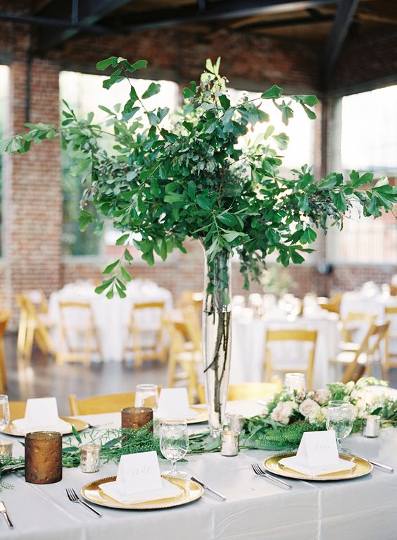 a natural greenery wedding centerpiece in a tall vase and a matching greenery runner