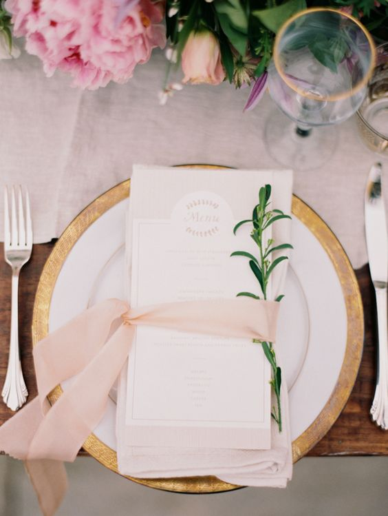 a stylish place setting with a lush table runner, blush ribbon and gilded rim chargers and glasses